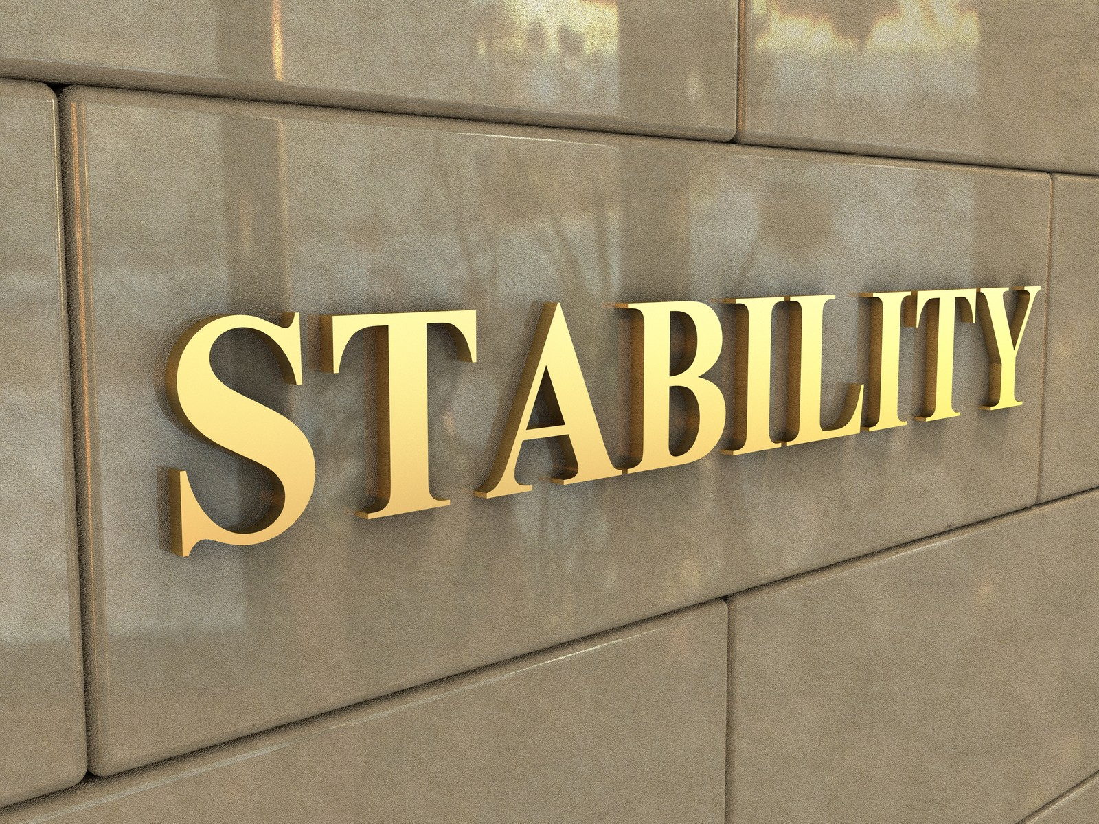 Stone wall with gold letters spelling out STABILITY