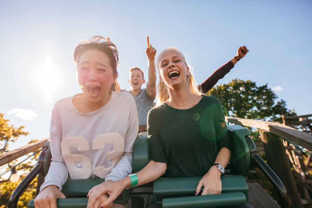 photo shows people going down a hill on a roller coaster, yelling and arms either in the air of clutching a bar