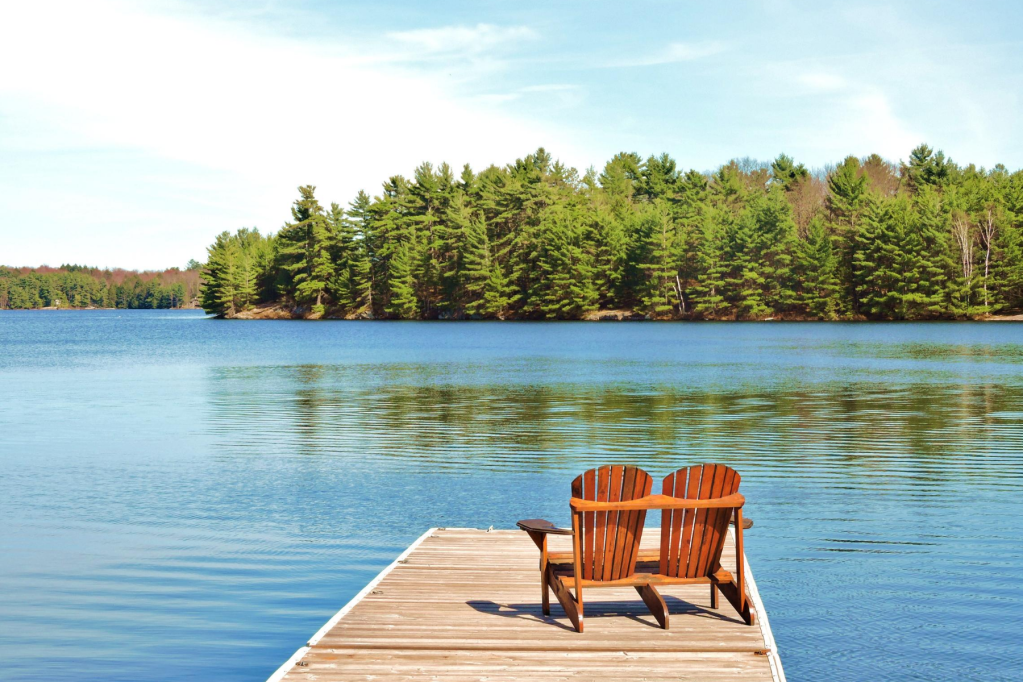 photo shows wooden chairs on wooden deck on a wooded lake